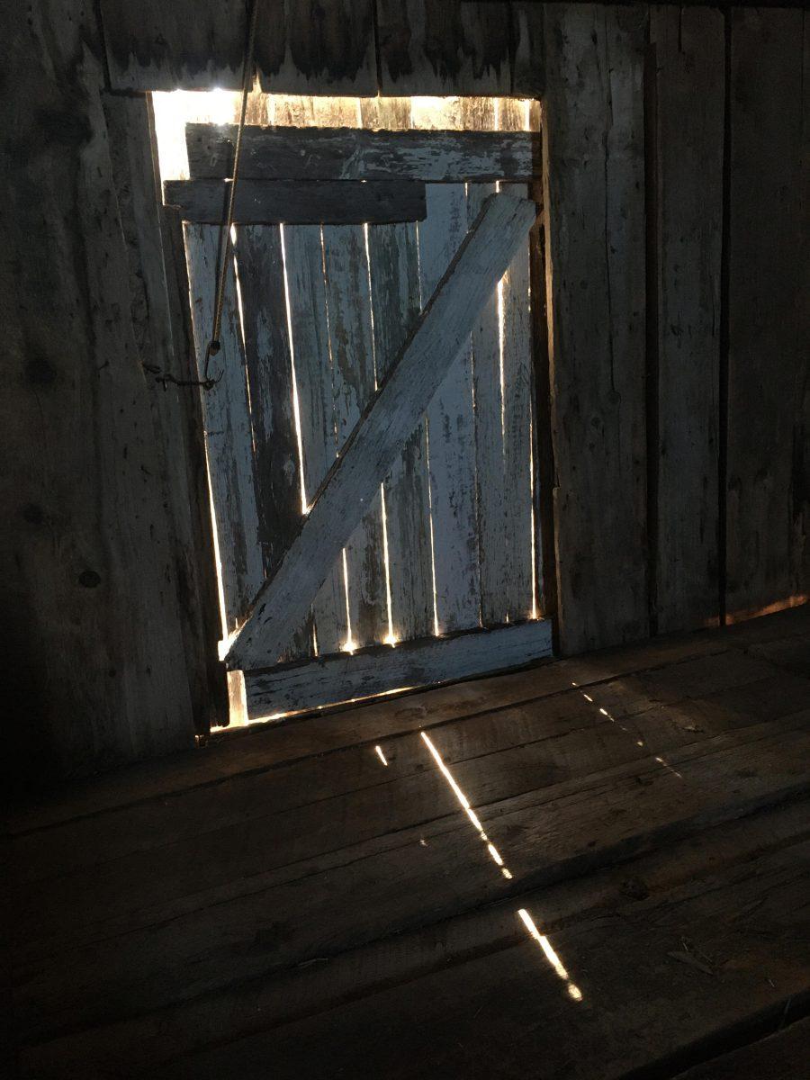 Old barn hayloft door with light shining through.