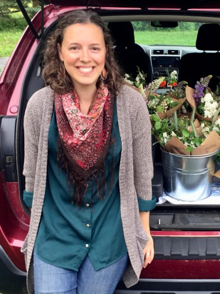 Michelle Darwin leaning against a car with market-ready cut flowers