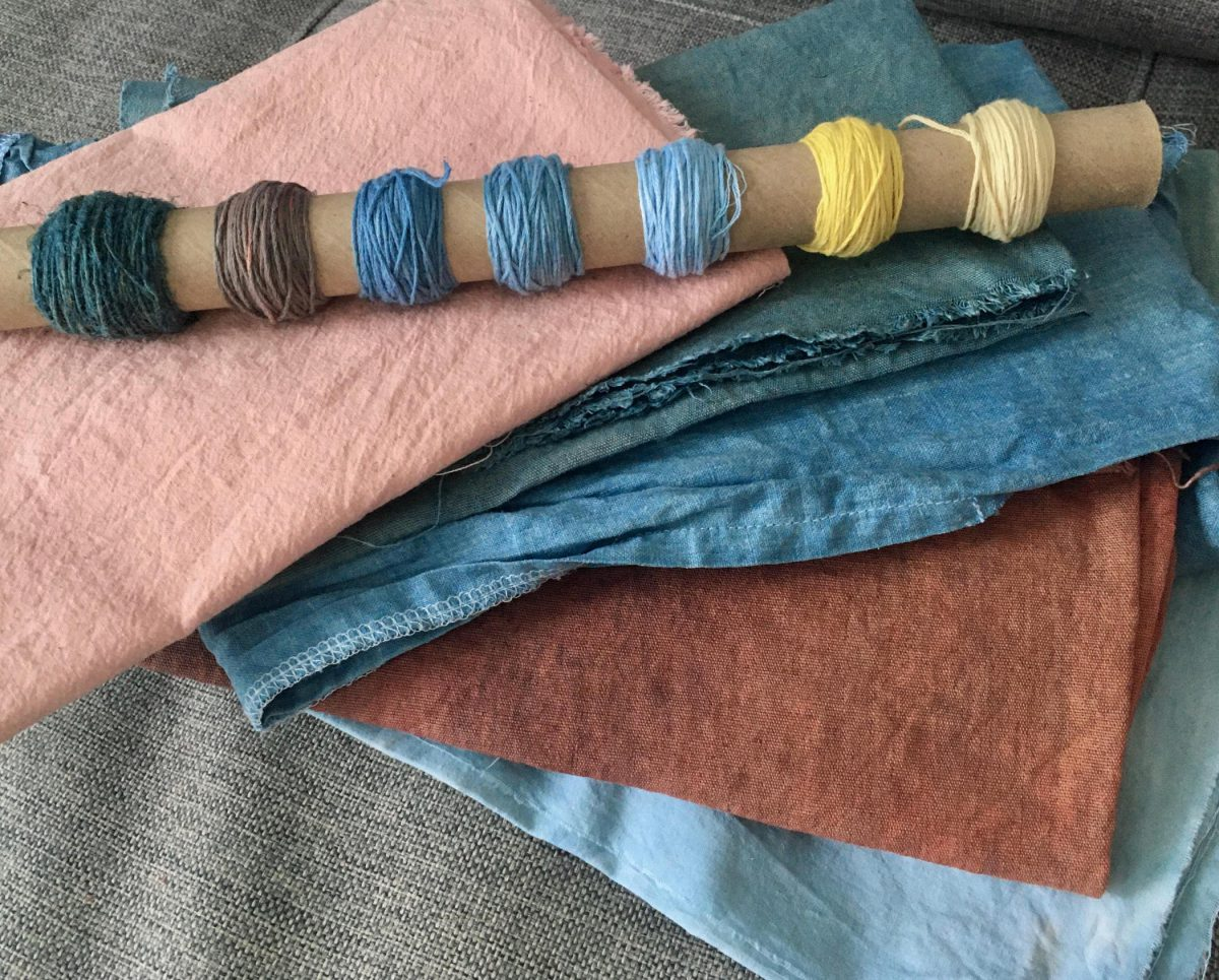 Textiles and embroidery thread dyed in pinks, blues, reds, and yellows