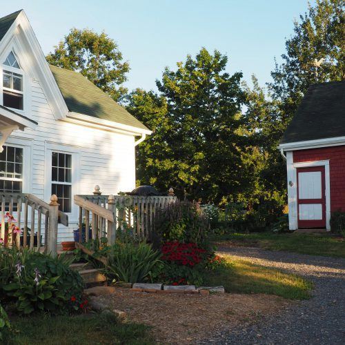 House, gardens, and barn in early morning light