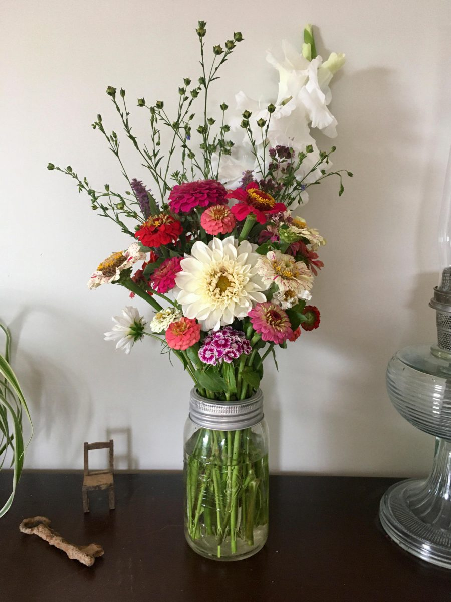 Vase of seasonal flowers including dahlia and zinnia, old rusted skeleton key, small handmade wooden dollhouse chair