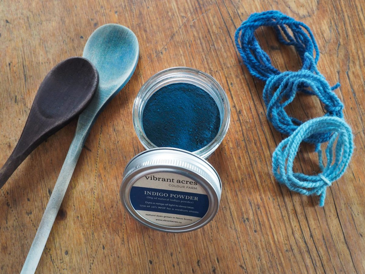 Indigo powder in a jar with Vibrant Acres logo, wooden dye spoons and yarn samples dyed blue