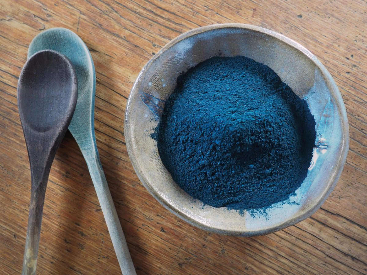 Bowl of indigo powder, wooden dye spoons stained brown and blue